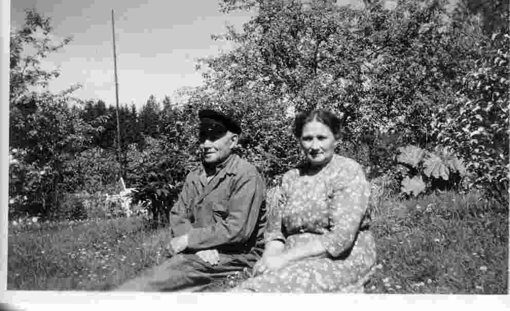 Ett medelålders par sitter i gräset.